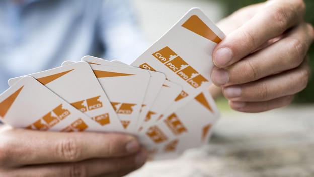 Eine Hand hält Jasskarten mit CVP-Logo.