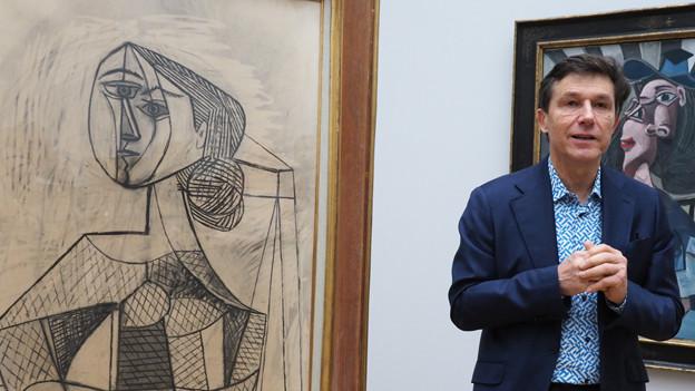Kunstmuseum-Direktor Helfenstein vor zwei Bildern.