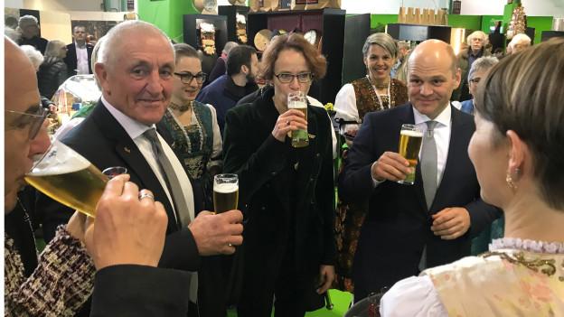Vier Politiker mit einem Bier Glas in der Hand.