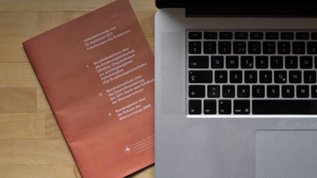 Abstimmungsbüchlein liegt neben Laptop