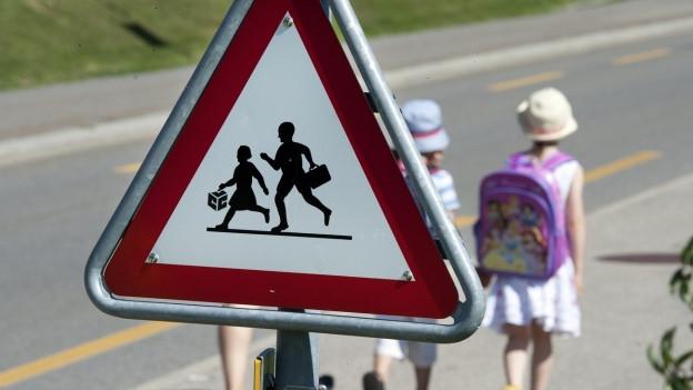 Kinder auf Schulweg mit Warntafel