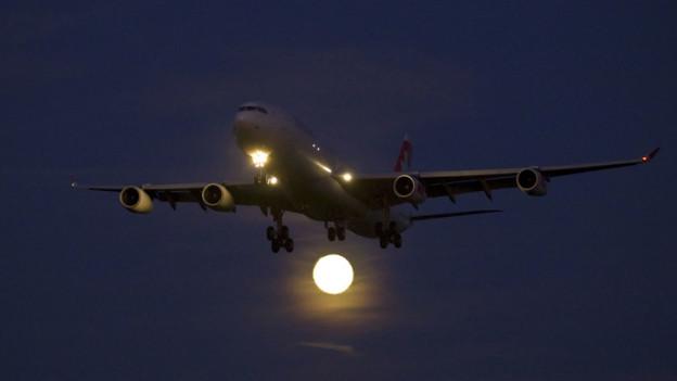 Flugzeug im Nachthimmel vor Vollmond.