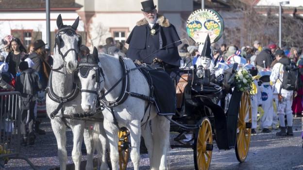 Eine Kutsche mit zwei Pferden an der Basler Fasnacht.