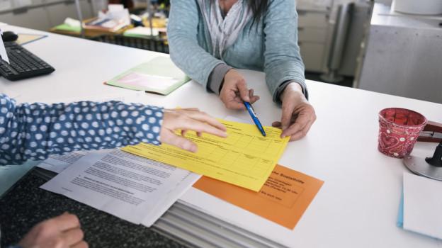 Betroffener und Betreuerin mit einen Sozialhilfe-Formular.
