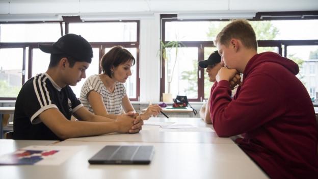 Ein Lehrerin mit drei Schülern im Klassenzimmer.