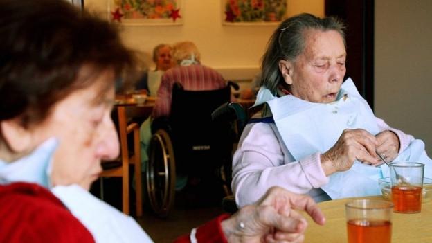 Zwei betagte Frauen an einem Esstisch.