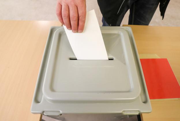 Eine Hand, die einen Zettel in eine Wahl-Urne wirft.