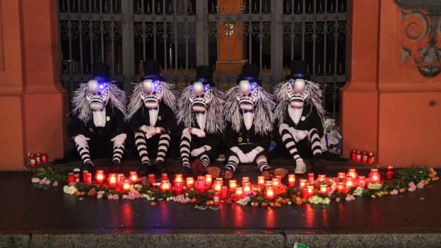 Waggis sitzen vor dem Rathaus, umringt von Grablichtern