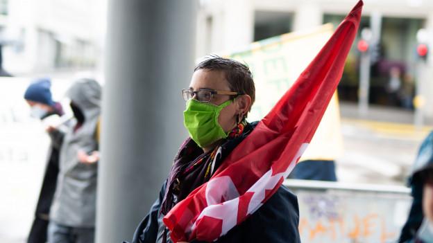 Tonja Zürcher an der Demo mit Mundschutz und Fahne