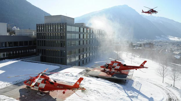 Drei Rettungshelikopter stehen auf dem Gelände des Spitals.