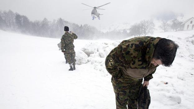 Zwei Soldaten ducken sich, weil ein Helikopter im Schnee landet und Schnee aufwirbelt.