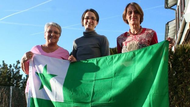 Barbara Pochanke (links), ihre Tochter Veronika sowie Verena Chaves-Walder (rechts) mit der grünen Esperanto-Fahne.