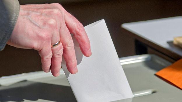 Mann steckt Abstimmungszettel in eine Wahlurne