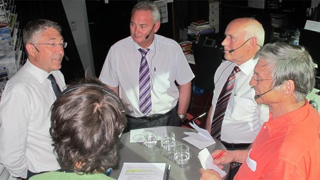 Vier herren mit der Moderatorin stehen um einen Tisch mit Mikrofonen.