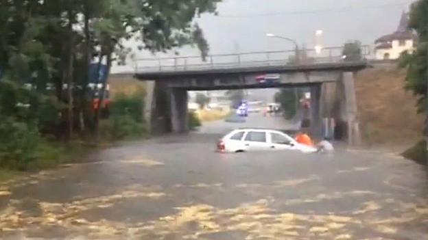 Ein Auto wird von den Wassermassen weggespült.