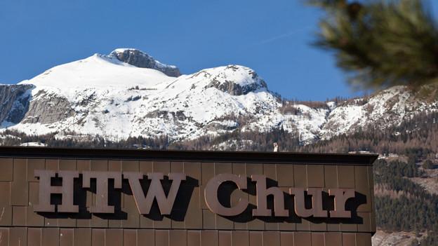 Ausschnitt GEbäude mit Schriftzug, Hintergrund mit verschneiten Bergen.