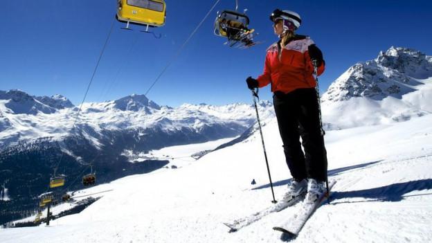 Eine Skifahrerin steht auf der Piste.