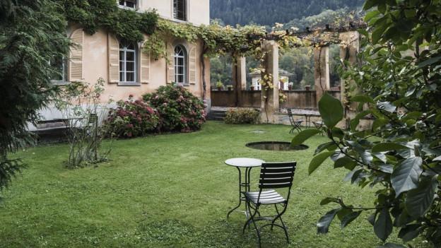 Altes Gebäude und Garten mit Rasen und Weinranken.