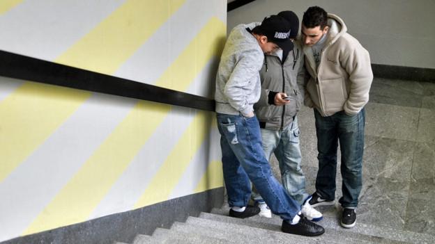 Drei Jugendliche in einem Schulhausgang.