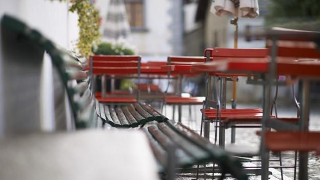 Leere Stühle in einer Gartenbeiz.