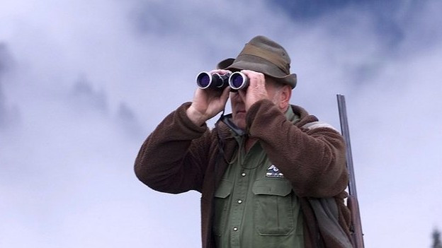 Ein Jäger schaut durch seinen Feldstecher.