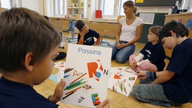 Ein Kind hält das Schulbuch «Passins» in den Händen.
