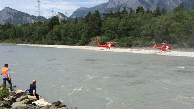 Bergfluss, am Ufer stehen REGA-Helikopter.
