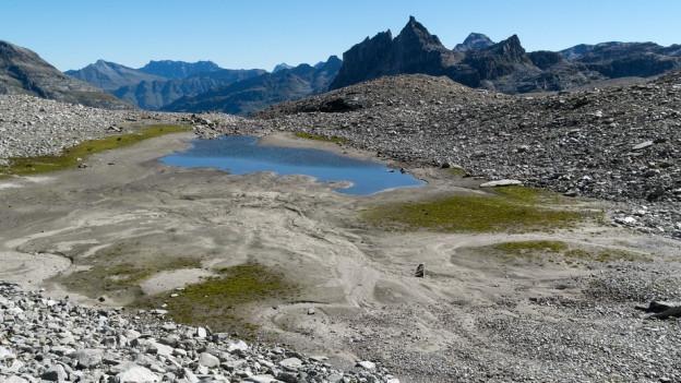 Ein türkis schimmernder See in den Bergen.