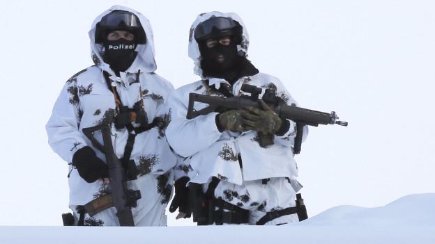 Soldaten mit Waffen und weisser Tarnkleidung beobachten Davos.