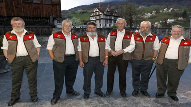 Die Wetterschmöcker stehen auf Dorfplatz. sie tragen ihr typisches Outfit - Faserpelzwesten mit Schwizerkreuz-Emblemen über der Brust.