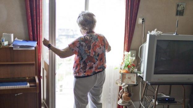 Ältere Frau steht an einem Fester in einem Alterszentrum.