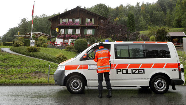 Ein Schwyzer Polizist vor einem Polizeibus.