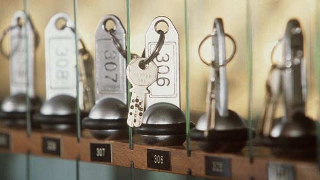 Zimmerschlüssel eines Hotels in einer Reihe.