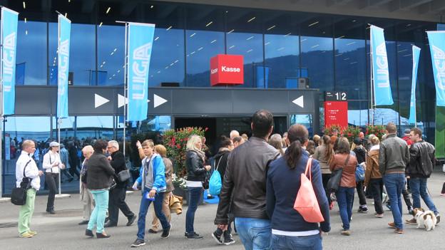 Menschen vor einer Messehalle in Luzern.