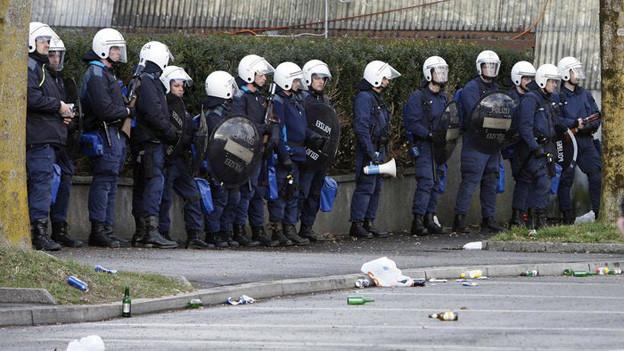 Polizisten, ausgerüstet mit Helmen und Schildern.