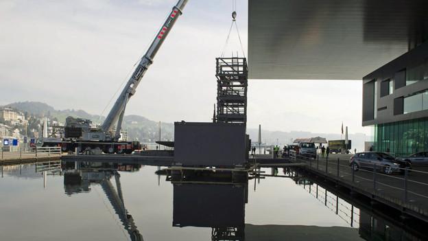 Ein Pneukran platziert ein Gerüst für die Sanierung des KKL Luzern.