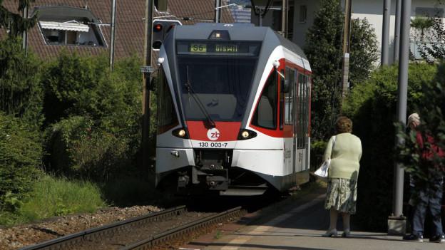Ein rot-weisser Zug der Zentralbahn. Daneben eine ältere Person, die auf dem Perron steht.