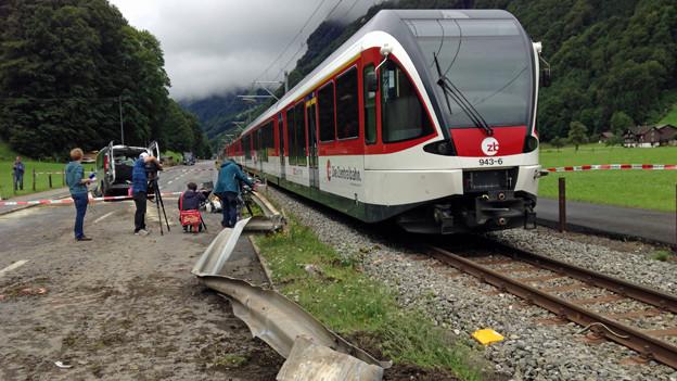 Ein rot-weisser Zug der Zentralbahn. Daneben Journalisten, die Aufnahmen vom Unfall machen.
