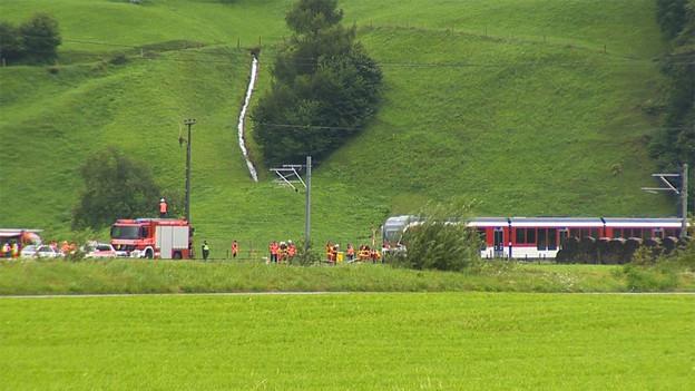 Ein rot-weisser Zug der Zentralbahn. Daneben Ambulanzen und Retter.