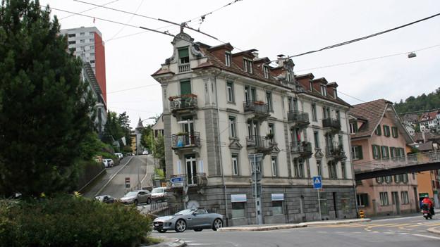 Ein graues Haus, davor die Hauptstrasse.
