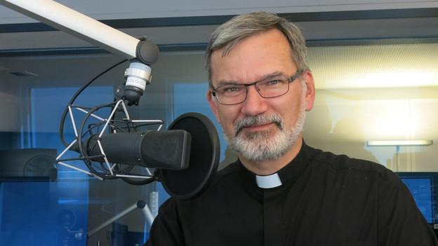 Ein Bischof mit schwarzem Hemd und Bart.