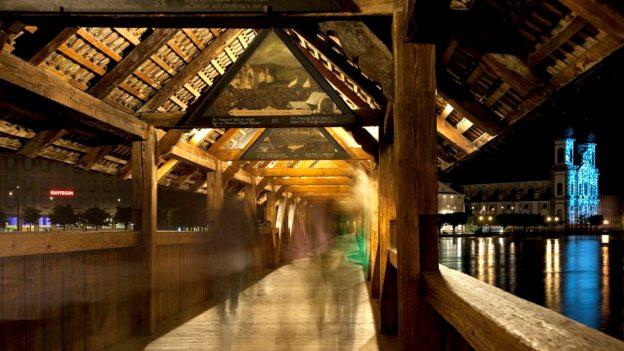 Eine Holzbrücke in Luzern in der Nacht mit Passanten.