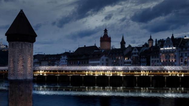 Die neue Inszenierung der Kapellbrücke in Luzern mit vielen kleinen weissen Lichtern.