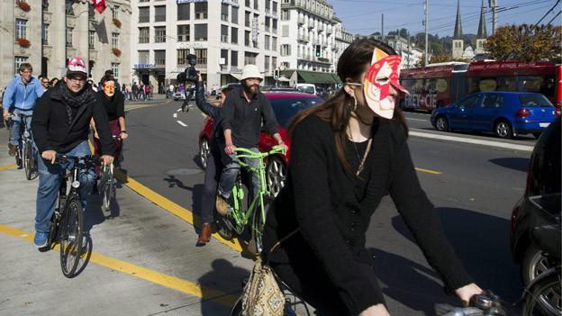 Junge Leute fahren maskiert auf Velos.