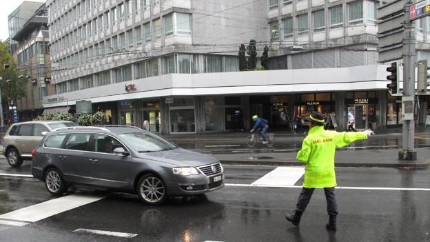 Eine Verkehrslotsin in gelbem Regenmantel mitten auf einer Strasse.