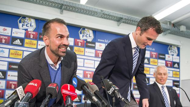 Zwei Männer sind daran, sich zu setzen. Vor ihnen eine Reihe von Mikrophonen.