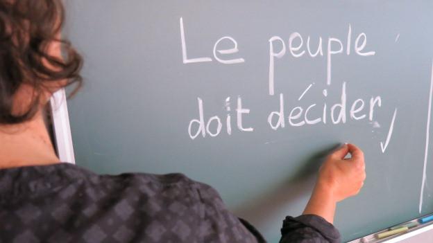 Eine Wandtafel mit einem französischen Satz.