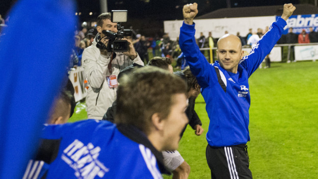 Fussballtrainer und Spieler freuen sich über einen Sieg.