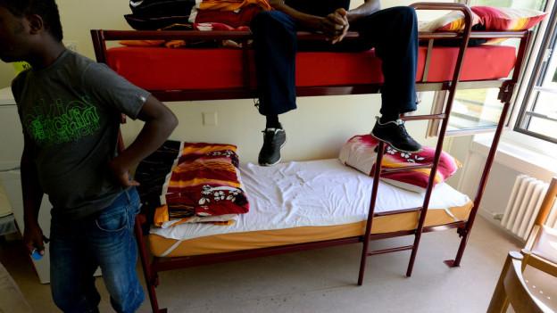 Zwei Asylsuchende in einem Zimmer. Einer sitzt auf dem Bett, der andere steht daneben.