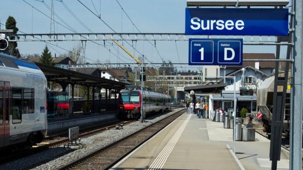 Am Bahnhof in Sursee halten Züge und Menschen steigen aus.